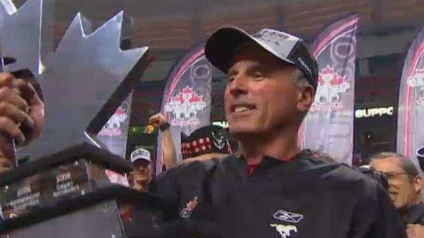 Calgary Stampeders Head Coach John Hufnagel holds up the West Final trophy.