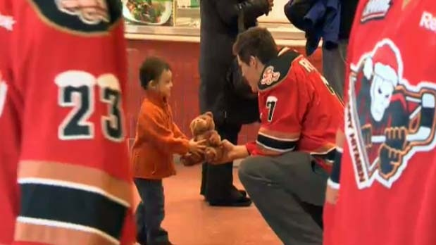 The Hitmen's Alex Roach hands a little fan a stuffed toy at Alberta Children's Hospital on Monday, Dec 3, 2012