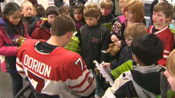 The players sign autographs for the kids.