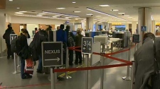Passengers wait in lineups for security screening