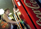 A teen helps herself to a drink from a pop machine.  (AP Photo/The Times/Greg Pearson)