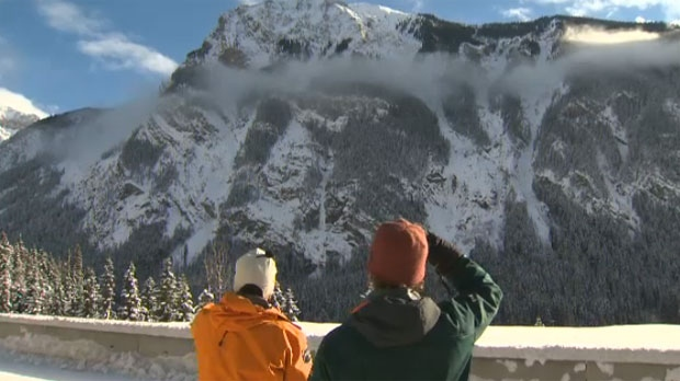 Two Parks Canada employees survey a mountain in Banff National Park