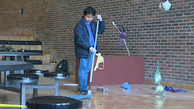 A man is seen cleaning up after a performance by an MRU student where he slaughtered a live chicken in plain view.