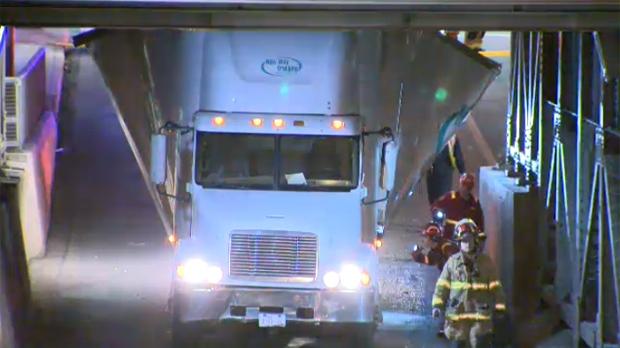 Semi truck and trailer wedged under bridge