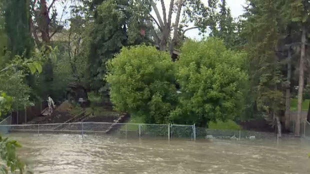 The water creeps up the yard of one of the homes along the Elbow River.
