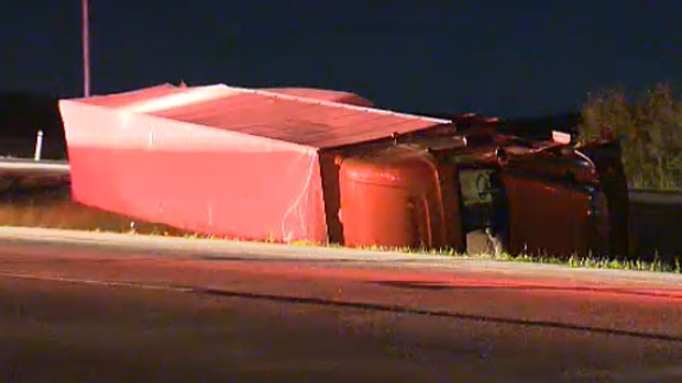 A semi truck is seen rolled onto its side in the median of Highway 1 just west of Cochrane. Three people were injured after it crashed into a moving truck.