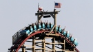 Visitors to Six Flags ride the Texas Giant as they crest the top of the tallest drop on the roller coaster ride in Arlington, Texas, Saturday Sept. 14, 2013. (AP / Tony Gutierrez)
