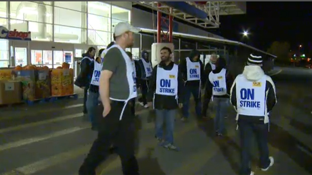 Workers march outside of the Sunridge Superstore location in Calgary
