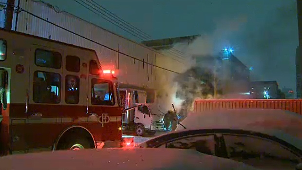 Smoke pours from the garage of a business in the downtown core. Fire crews were called there at about 3 a.m. and found material burning inside a dumpster.