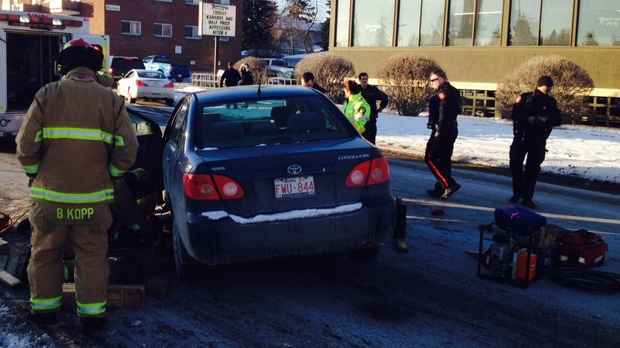 Emergency crews attend to a man trapped underneath a vehicle at the intersection of 16 Ave. and 19 St. N.W.