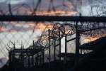 In this Nov. 21, 2013 file photo, reviewed by the U.S. military, dawn arrives at the now closed Camp X-Ray, which was used as the first detention facility for al Qaeda and Taliban militants who were captured after the Sept. 11 attacks at Guantanamo Bay Naval Base, Cuba. (AP / Charles Dharapak)