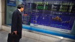 A man stops and looks at Japan's Nikkei stock update on an electric board at a securities firm in Tokyo, Wednesday, March 12, 2014. (AP / Junji Kurokawa)