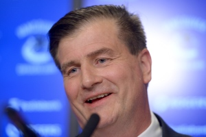 In this file photo, Jim Benning, general manager of the Vancouver Canucks, smiles at a news conference in Vancouver, Friday May 23, 2014. (Jonathan Hayward / THE CANADIAN PRESS)