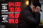In this Tuesday, Dec. 16, 2014, file photo, a man walks by a sign advertising currencies of an exchange office in Moscow. Russia has been badly affected by the slide in oil prices in 2014, and the ruble has plunged despite big increases in interest rates as much of Russia's economy is based on energy. (AP Photo/Alexander Zemlianichenko)