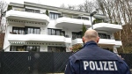 A police officer stands in front of an apartment building where they believe Andreas Lubitz, the co-pilot of the crashed Germanwings airliner jet, lived in Duesseldorf. (AP / Martin Meissner)