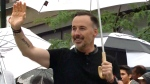 David Furnish waves to the crowd during the Pride parade in downtown Toronto on Sunday, June 28, 2015.