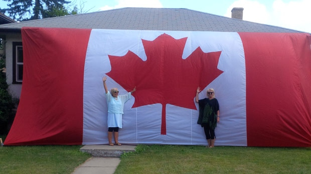 A home on 33 Avenue Southwest in Marda Loop is draped in a massive Canadian flag