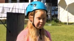 Nicole Weutherick dons a helmet at the climbing wall during leadership training at Easter Seals Camp Horizon