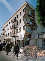 In this Jan. 18, 1994, file photo, California National Guardsman walk past a Hollywood apartment building damaged by a deadly earthquake in Los Angeles. (AP / Kevork Djansezian)