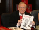 In this Nov. 15, 2007 photo, Hugh Hefner smiles while signing copies of the Playboy calendar and Playboy Cover To Cover: The 50's DVD box set in Los Angeles. (Ian West/PA via AP)