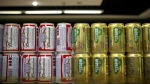 Cans of Budweiser beer, owned by AB InBev, sit next to cans of Snow beer, in which SABMiller has a 49 per cent ownership stake, on a grocery store shelf in Beijing on Thursday, Oct. 15, 2015. (AP / Mark Schiefelbein)