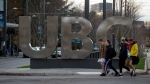 Young men walk past large letters spelling out 'UBC' at the University of British Columbia in Vancouver, B.C., on Nov. 22, 2015. (Darryl Dyck / THE CANADIAN PRESS)