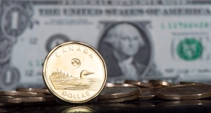 The Canadian dollar coin is displayed next to the U.S. dollar Friday, Jan. 30, 2015 in Montreal. (Paul Chiasson/THE CANADIAN PRESS)