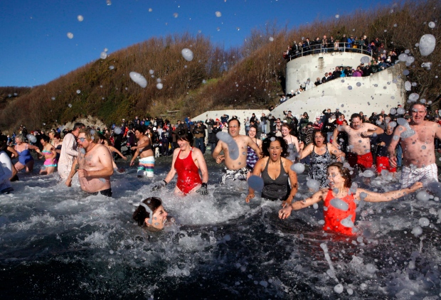People brave the cold water temperatures of the Pacific Ocean to take part in the annual polar bear swim held this year at Dallas Beach in Victoria, B.C., Friday, Jan. 1, 2016. (Chad Hipolito / THE CANADIAN PRESS)