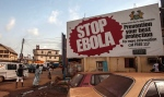 People pass a banner reading 'STOP EBOLA' forming part of Sierra Leone's Ebola free campaign in the city of Freetown, Sierra Leone on Friday, Jan. 15, 2016. (AP / Aurelie Marrier d'Unienville)