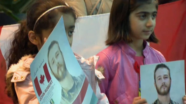 Two young girls hold photos of John Gallagher during Sunday's vigil for the fallen soldier