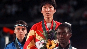 In this Sunday, July 28, 1996 file photo, women's 5,000 meters gold medalist Wang Junxia of China, center, is flanked by Pauline Konga of Kenya, right, silver, and Roberta Brunet of Italy, bronze during the medal presentation ceremony at the 1996 Summer Olympic Games in Atlanta. (AP / Ed Reinke)