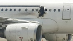 A hole is photographed in a plane operated by Daallo Airlines as it sits on the runway of the airport in Mogadishu, Somalia on Tuesday, Feb. 2, 2016. (AP)