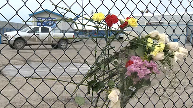 Flowers are seen in the fence at Canada Olympic Park in southwest Calgary, put there by mourners of the two teen boys killed in a crash on Saturday.