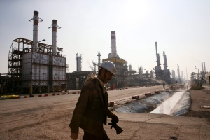 In this Dec. 22, 2014 file photo, an Iranian oil worker makes his way through Tehran's oil refinery south of the capital Tehran, Iran. (Vahid Salemi / AP Photo)