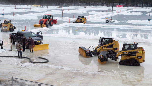 Workers remove water from the surface of Ralston Lake, the venue for the World Pond Hockey Championship, in Plaster Rock, N.B. on Thursday, February 25, 2016. Rain and warm temperatures are presenting challenges for the organizers as they ready the rinks for the four-day tournament. (THE CANADIAN PRESS/Andrew Vaughan)