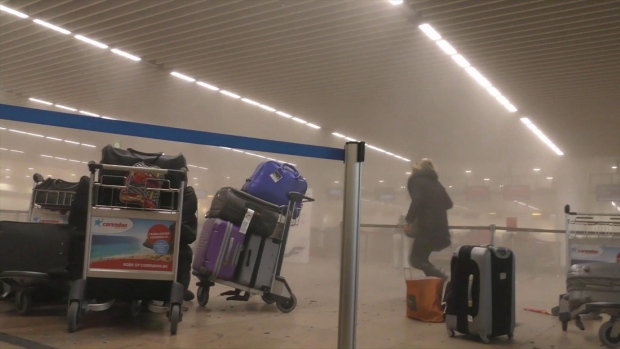 An unidentified traveller runs in a smoke filled terminal at Brussels Airport, in Brussels after explosions Tuesday, March 22, 2016. (Ralph Usbeck)