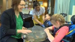 Music therapist Sarah Van Peteghen plays a percussion shaker with Reilly Harris and Ryan Hamm during a therapy session