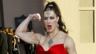 Joanie Laurer, former pro wrestler known as Chyna, flexes her bicep as she arrives at the 31st annual American Music Awards, in Los Angeles on Nov. 16, 2003. (AP / Kevork Djansezian)