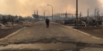 An RCMP officer surveys the damage on a street in Fort McMurray, Alta., Friday, May 6, 2016. (RCMP Alberta / Twitter)
