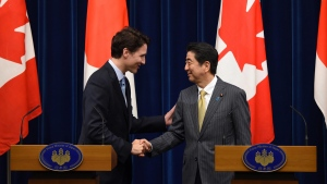 Canadian Prime Minister Justin Trudeau, left, shakes hands with his Japanese counterpart Shinzo Abe in Tokyo on May 24, 2016. (Toru Yamanaka / Pool Photo via AP)