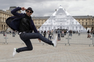 Street artist JR poses in front the Louvre Pyramid in Paris, Tuesday, May 24, 2016. For his latest bold project, street artist JR is creating an eye-tricking installation at the Louvre Museum that makes it seem as if the huge glass pyramid at the heart of the courtyard has disappeared. (AP Photo/Francois Mori)