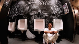 Winnipeg artist Nereo Eugenio sits by his Donald Trump piece that he created in the washroom at the District Stop nightclub in Winnipeg, on May 25, 2016. (John Woods / THE CANADIAN PRESS)
