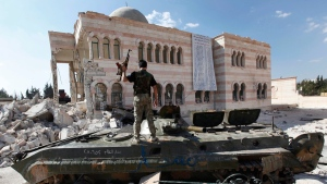 In this Sept. 23, 2012 file photo, a Free Syrian Army soldier stands on a damaged Syrian military tank in front of a damaged mosque in the Syrian town of Azaz, near Aleppo, Syria. (Hussein Malla / AP)
