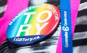Delegates Natalie Pon wears a lesbian and gay Tory button as she waits for the results in the vote to change the wording of the traditional definition of marriage in the conservative policies at the Conservative Party of Canada convention in Vancouver, Saturday, May 28, 2016 (Jonathan Hayward / THE CANADIAN PRESS)