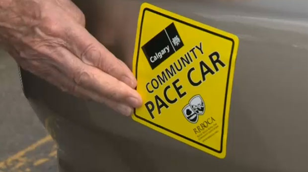 A resident of northwest Calgary places a Community Pace Car Program sticker on his vehicle