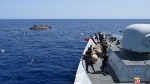An Italian Navy ship approaches an overturned boat off the Libyan coast, Wednesday, May 25, 2016. (Marina Militare via AP Photo)