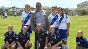 Mayor Nenshi poses for a photo with members of two soccer teams during the grand opening of New Brighton Athletic Park
