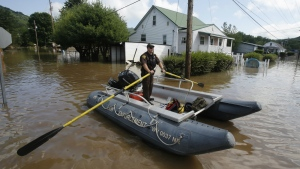 Lt. Dennis Feazell, of the West Virginia Department of Natural Resources, rows his boat as he and a co-worker search flooded homes in Rainelle, W. Va. on Saturday, June 25, 2016. (AP / Steve Helber)