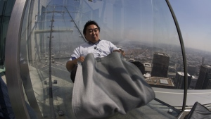 People slide down the Skyslide, a glass slide 70 floors up on the outside of the US Bank Tower. (AFP PHOTO/DAVID MCNEW)