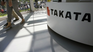 Visitors walk by a Takata Corp. desk at an automaker's showroom in Tokyo on May 4, 2016. (AP / Shizuo Kambayashi)